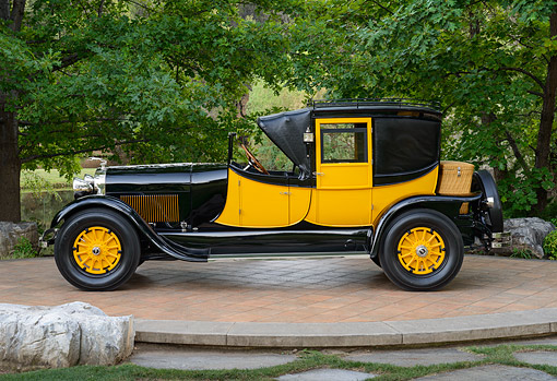 AUT 18 RK0840 01 © Kimball Stock 1927 Lincoln Coaching Brougham Yellow And Black Profile View On Brick By Trees