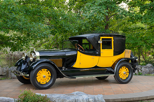 AUT 18 RK0841 01 © Kimball Stock 1927 Lincoln Coaching Brougham Yellow And Black 3/4 Side View On Brick By Trees