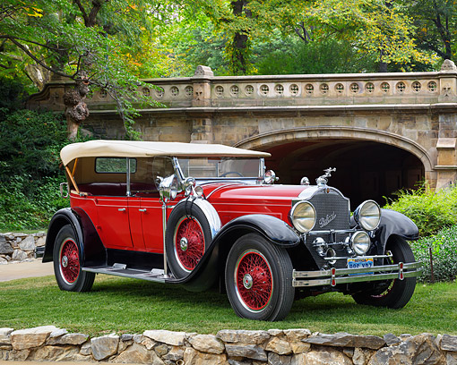 AUT 18 RK0869 01 © Kimball Stock 1929 Packard 640 Dual-Windshield Phaeton Red And Black 3/4 Front View By Trees And Bridge