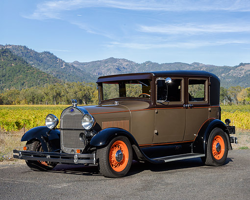 AUT 18 RK0871 01 © Kimball Stock 1928 Ford Model A Sedan Brown 3/4 Front View By Mountains And Vineyards