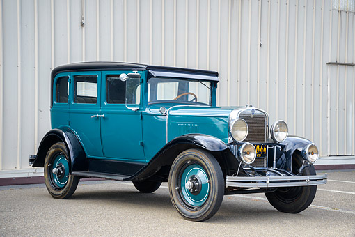 AUT 18 RK0873 01 © Kimball Stock 1929 Chevrolet Series AC International 4-Door Sedan Blue Green 3/4 Front View By Tall Gray Building