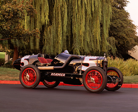 AUT 18 RK0021 03 © Kimball Stock 1920 Roamer Boardtrack Racing Car Black 3/4 Front View On Pavement By Trees
