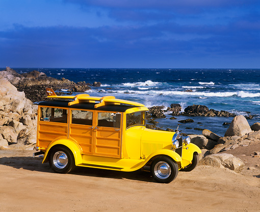 AUT 18 RK0037 04 © Kimball Stock 1929 Ford Woody Yellow With Surfboard 3/4 Front View On Sand By Ocean