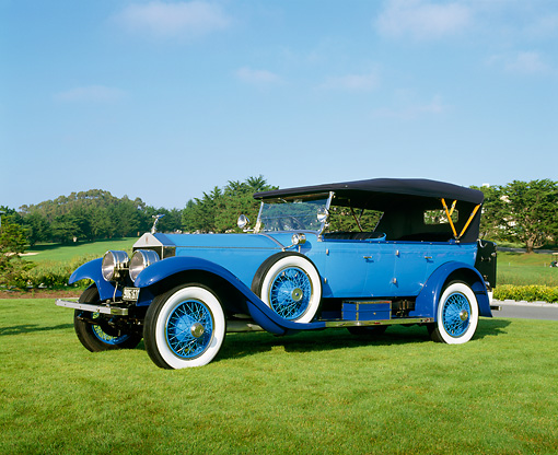 AUT 18 RK0060 02 © Kimball Stock 1923 Rolls-Royce Silver Ghost Blue 3/4 Front View On Grass Blue Sky