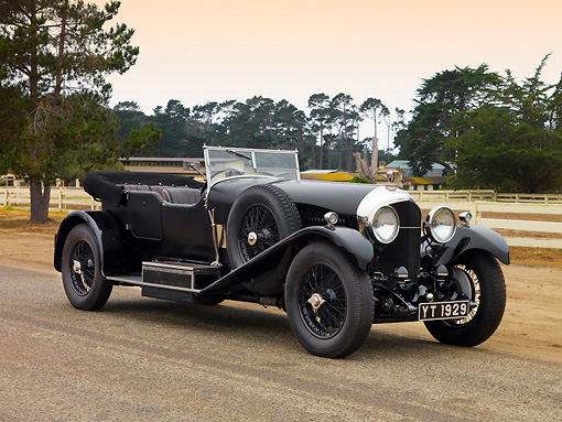 AUT 18 RK0297 01 © Kimball Stock 1927 Bentley 6.5 Liter Vanden Plas Convertible Black Front 3/4 View On Pavement By Fence Trees