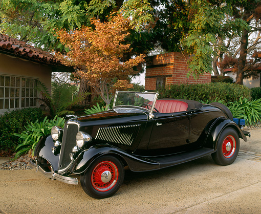 AUT 19 RK0213 03 © Kimball Stock 1933 Ford Roadster Black 3/4 Front View On Pavement By Trees And Buildings