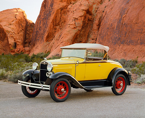 AUT 19 RK0384 01 © Kimball Stock 1931 Ford Model A Deluxe 40B Roadster Yellow 3/4 Front View On Pavement By Red Rock