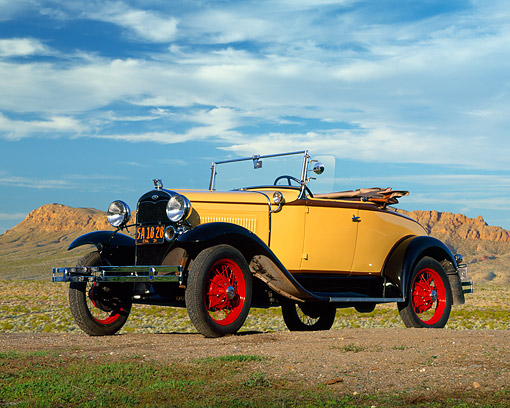 AUT 19 RK0389 01 © Kimball Stock 1931 Ford Model A Deluxe Roadster Yellow 3/4 Front View On Dirt In Desert