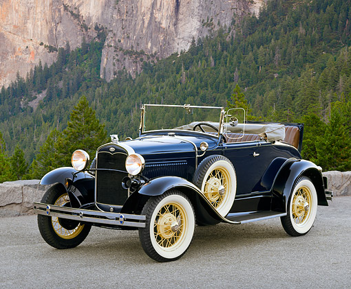AUT 19 RK0405 03 © Kimball Stock 1931 Ford Model A Deluxe Roadster Blue 3/4 Side View On Pavement By Mountain And Trees