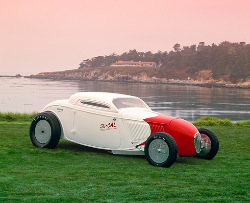 AUT 19 RK0424 10 © Kimball Stock 1934 Ford So-Cal Special Coupe 3/4 Front View Red And White On Grass By Water Red Sky Pebble Beach