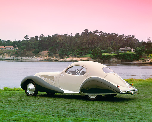 AUT 19 RK0434 05 © Kimball Stock 1938 Talbot Lago Tear Drop Coupe Green 3/4 Rear View On Grass By Water Red Sky Pebble Beach