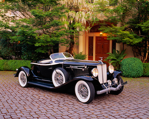 AUT 19 RK0505 08 © Kimball Stock 1933 Auburn V12 Boat-Tail Speedster Black 3/4 Side View On Pavement By Trees And Bushes