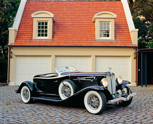 AUT 19 RK0508 01 © Kimball Stock 1933 Auburn V-12 Boat-tail Speedster Black 3/4 Side View On Driveway By Garage
