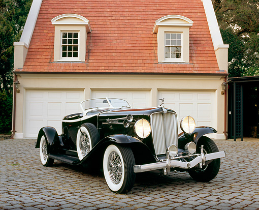 AUT 19 RK0510 01 © Kimball Stock 1933 Auburn V-12 Boat-tail Speedster Black 3/4 Front View On Driveway By Garage