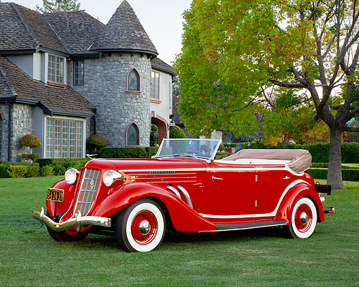 AUT 19 RK0614 03 © Kimball Stock 1935 Auburn 851 Supercharged Convertible Red And Cream 3/4 Side View On Grass By House