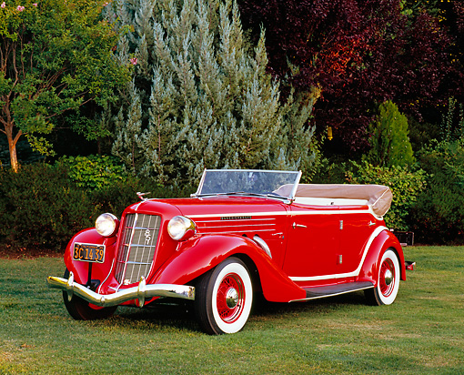 AUT 19 RK0615 02 © Kimball Stock 1935 Auburn 851 Supercharged Convertible Red And Cream Front 3/4 View On Grass By Trees