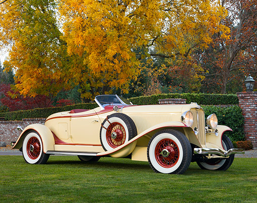 AUT 19 RK0686 01 © Kimball Stock 1932 Auburn V-12 Boattail Speedster 160 Yellow And Maroon Front 3/4 View On Grass By Autumn Trees