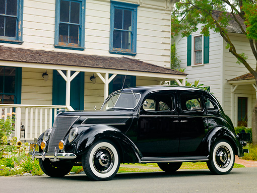 AUT 19 RK0747 01 © Kimball Stock 1937 Ford Deluxe Touring Sedan Black 3/4 Front View On Pavement By House