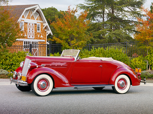 AUT 19 RK0754 01 © Kimball Stock 1936 Packard 120 Convertible Coupe Red 3/4 Front View On Pavement By Trees