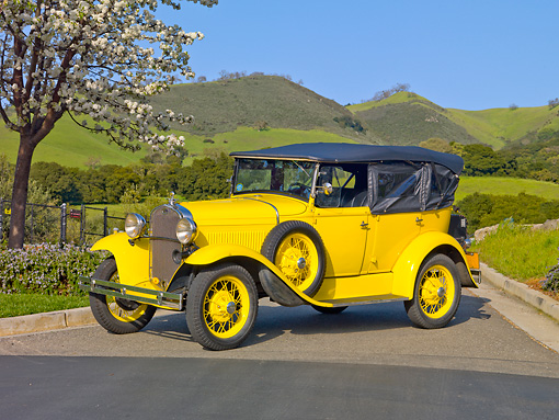AUT 19 RK0768 01 © Kimball Stock 1930 Ford Model A Phaeton STD Yellow 3/4 Side View On Pavement By Trees