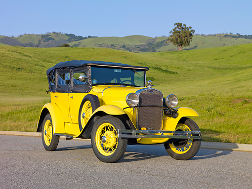 AUT 19 RK0770 01 © Kimball Stock 1930 Ford Model A Phaeton STD Yellow 3/4 Front View On Pavement By Grassy Hills