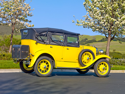 AUT 19 RK0771 01 © Kimball Stock 1930 Ford Model A Phaeton STD Yellow 3/4 Rear View On Pavement By Trees