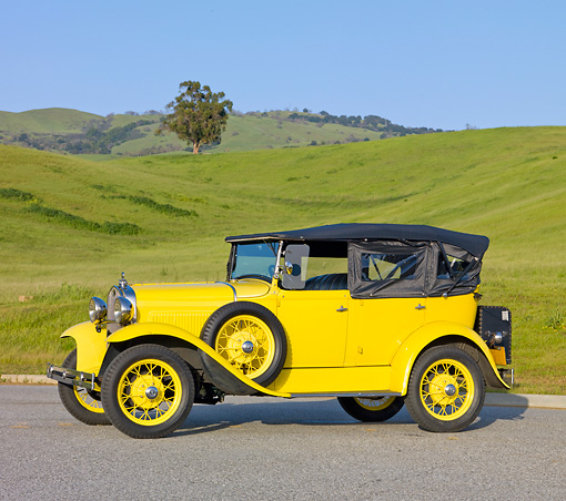 AUT 19 RK0773 01 © Kimball Stock 1930 Ford Model A Phaeton STD Yellow 3/4 Side View On Pavement By Grassy Hills