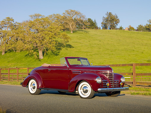 AUT 19 RK0777 01 © Kimball Stock 1939 Plymouth P8 Convertible Dark Cranberry 3/4 Side View On Pavement By Fence And Grassy Hill