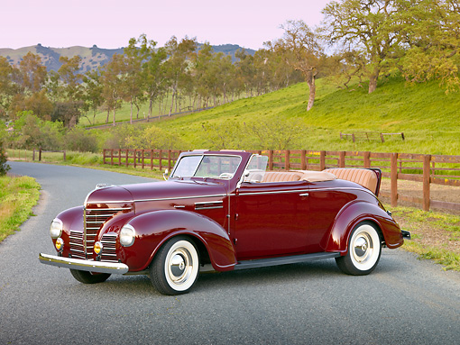 AUT 19 RK0779 01 © Kimball Stock 1939 Plymouth P8 Convertible Dark Cranberry 3/4 Front View On Pavement By Fence And Grassy Hill