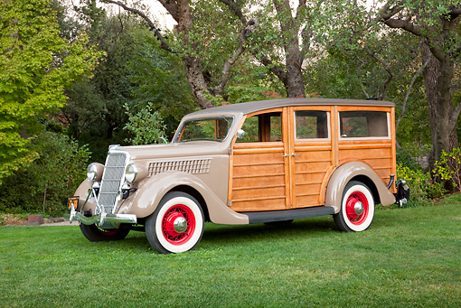 AUT 19 RK0847 01 © Kimball Stock 1935 Ford Woodie Beige 3/4 Side View On Grass By Trees