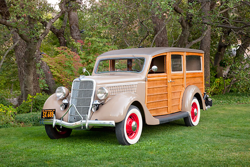 AUT 19 RK0848 01 © Kimball Stock 1935 Ford Woodie Beige 3/4 Front View On Grass By Trees