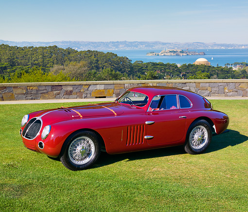 AUT 19 RK0850 01 © Kimball Stock 1939 Alfa Romeo 6C 2500 SS Berlinetta Aerodinamica Burgundy 3/4 Side View On Grass By San Francisco Bay