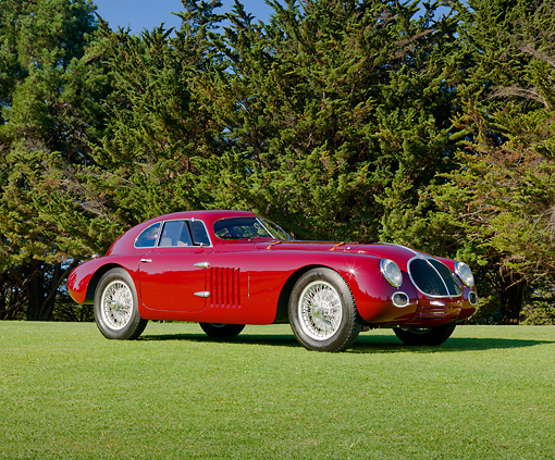 AUT 19 RK0852 01 © Kimball Stock 1939 Alfa Romeo 6C 2500 SS Berlinetta Aerodinamica Burgundy 3/4 Side View On Grass By Trees