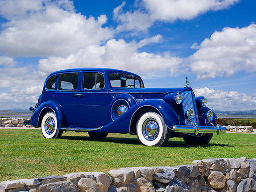 AUT 19 RK0870 01 © Kimball Stock 1937 Packard Super Eight Sedan Blue 3/4 Side View On Grass Against Blue Sky