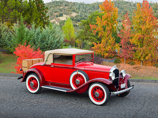 AUT 19 RK0887 01 © Kimball Stock 1931 Plymouth Convertible Coupe Red 3/4 Front View On Pavement By Autumn Trees
