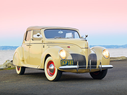 AUT 19 RK0925 01 © Kimball Stock 1939 Lincoln Zephyr Convertible Cream 3/4 Front View On Pavement By Water At Dusk