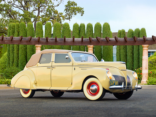 AUT 19 RK0926 01 © Kimball Stock 1939 Lincoln Zephyr Convertible Cream 3/4 Side View On Pavement By House And Shrubs