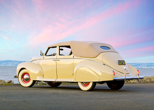 AUT 19 RK0927 01 © Kimball Stock 1939 Lincoln Zephyr Convertible Cream 3/4 Rear View On Pavement By Water At Dusk