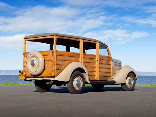 AUT 19 RK0932 01 © Kimball Stock 1936 Ford Woodie Station Wagon Brown 3/4 Rear View On Pavement By Water