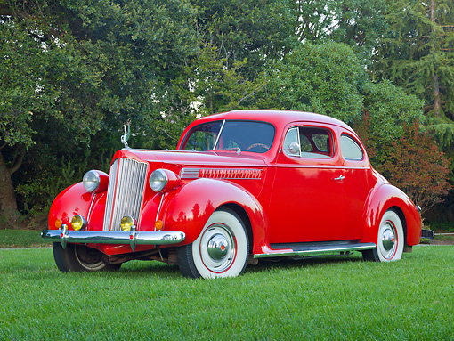 AUT 19 RK0952 01 © Kimball Stock 1939 Packard 2/4-Passenger Coupe Red 3/4 Front View On Grass By Trees