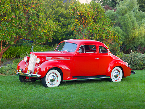 AUT 19 RK0953 01 © Kimball Stock 1939 Packard 2/4-Passenger Coupe Red 3/4 Side View On Grass By Trees