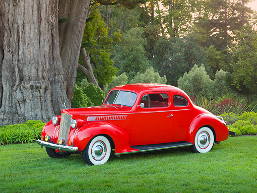 AUT 19 RK0955 01 © Kimball Stock 1939 Packard 2/4-Passenger Coupe Red 3/4 Side View On Grass By Trees