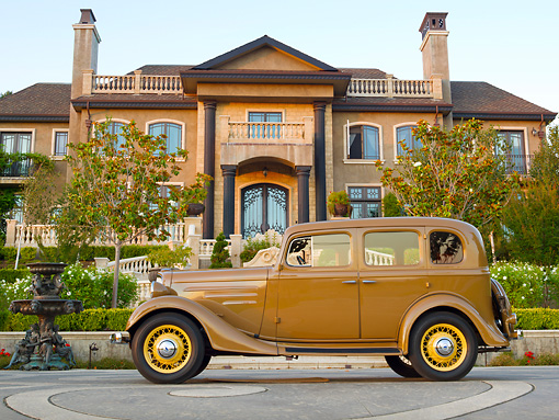 AUT 19 RK0957 01 © Kimball Stock 1935 Chevrolet Sedan Hollywood Tan Profile View On Pavement By Mansion