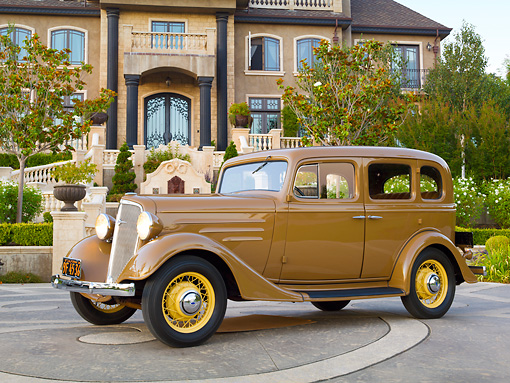 AUT 19 RK0959 01 © Kimball Stock 1935 Chevrolet Sedan Hollywood Tan Profile View On Pavement By Mansion
