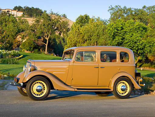 AUT 19 RK0964 01 © Kimball Stock 1935 Chevrolet Sedan Hollywood Tan Profile View On Pavement By Lawn