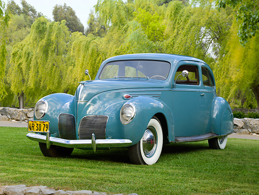 AUT 19 RK1017 01 © Kimball Stock 1938 Lincoln Zephyr Coupe Sedan Avon Blue 3/4 Front View On Grass By Trees