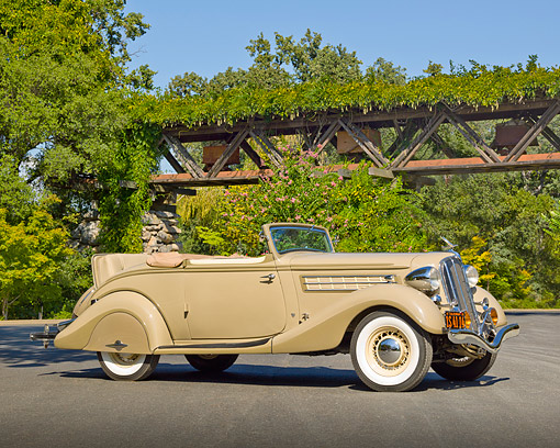AUT 19 RK1019 01 © Kimball Stock 1935 Hudson Convertible Pepper Tan 3/4 Side View On Pavement By Gate And Trees