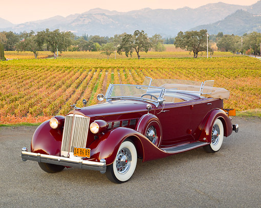 AUT 19 RK1028 01 © Kimball Stock 1936 Packard Super 8 Dual Cowl Phaeton Maroon 3/4 Front View On Pavement By Vineyard