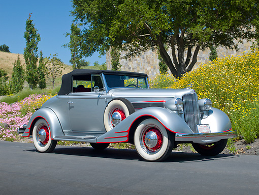 AUT 19 RK1032 01 © Kimball Stock 1934 Pontiac Convertible Silver With Red Trim 3/4 Front View On Pavement By Trees And Flowers