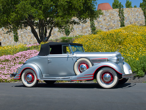 AUT 19 RK1034 01 © Kimball Stock 1934 Pontiac Convertible Silver With Red Trim Profile View On Pavement By Trees And Flowers